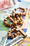 rosary beads on euro currency