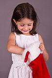 Little girl getting a gift from her Christmas stocking