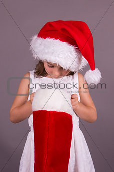 Little girl looking in her Christmas stocking