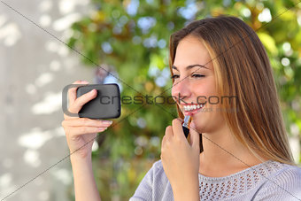 Beautiful woman making up using a smart phone as a mirror