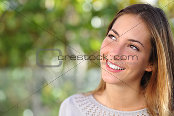 Beautiful woman smiling with a perfect teeth and looking above