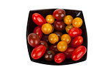 Cherry tomatoes in black plate isolated on white background