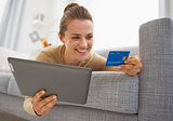 Closeup on credit card in hand of young woman laying on sofa wit