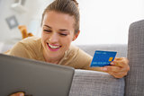 Smiling young woman with credit card using tablet pc while layin