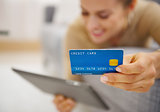 Closeup on credit card in hand of young woman laying on couch wi