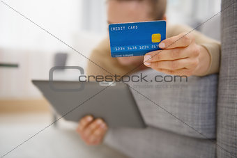 Closeup on credit card in hand of young woman laying on divan wi
