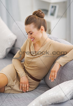 Smiling young housewife sitting on sofa