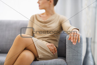 Closeup on young housewife sitting on couch