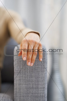 Closeup on hand of young housewife sitting on couch