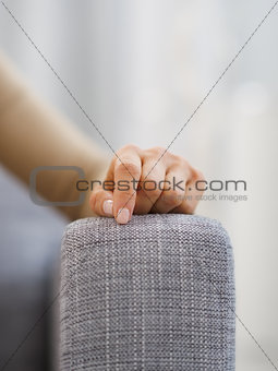 Closeup on hand of stressed woman sitting on couch