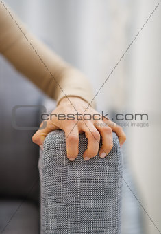 Closeup on hand of stressed woman sitting on sofa