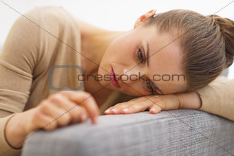 Frustrated young housewife sitting on couch