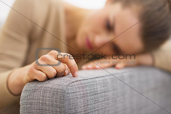 Closeup on hand of frustrated young housewife sitting on couch