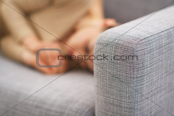 Closeup on couch and frustrated young housewife in background
