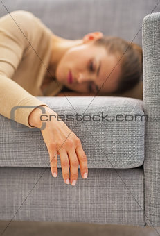 Closeup on hand of frustrated young housewife laying on sofa