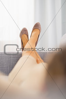 Closeup on leg of young housewife laying on sofa