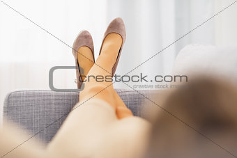 Closeup on leg of young housewife laying on couch