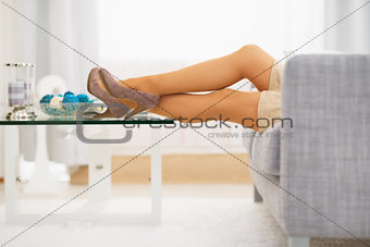 Closeup on leg of young woman laying on sofa