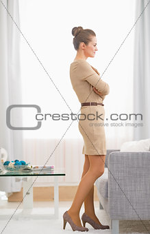 Full length portrait of young housewife standing in living room