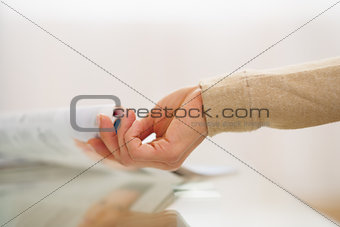 Closeup on hand of woman taking magazine from table