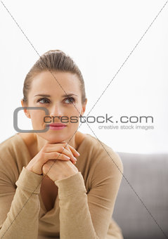 Portrait of thoughtful young housewife sitting on sofa