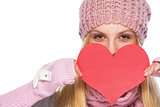Happy girl in winter clothes hiding behind heart shaped valentin