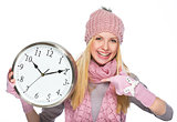 Smiling girl in winter clothes pointing on clock