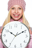 Smiling girl in winter clothes showing clock