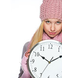 Girl in winter clothes showing clock