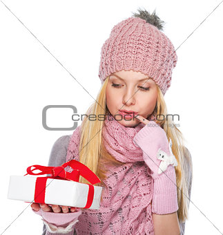 Thoughtful girl in winter clothes looking on christmas present b