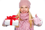 Closeup on christmas present box in hand of smiling girl in wint