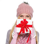 Girl in winter clothes hiding behind christmas presenting box