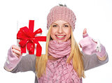 Smiling girl in winter clothes showing christmas presenting box