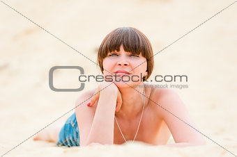 Girl in denim shorts tan while lying on the sand