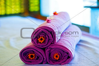 Towels on the bed in a spa decorative decorated.