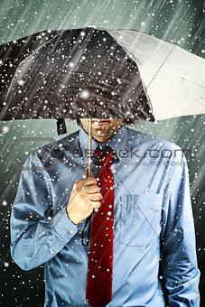 Businessman with umbrella in storm