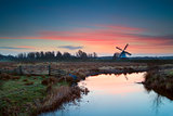 pink sunrise over Dutch windmill and river