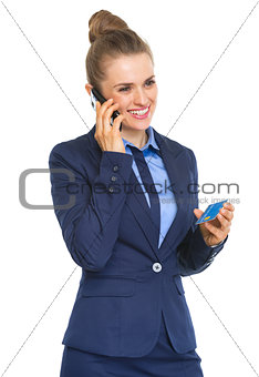 Smiling business woman with credit card talking cell phone