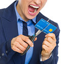 Closeup on angry business woman cutting credit card with scissor