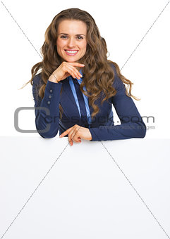Smiling business woman showing blank billboard