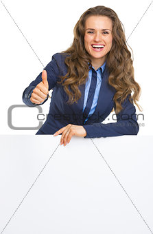 Smiling business woman showing blank billboard and thumbs up