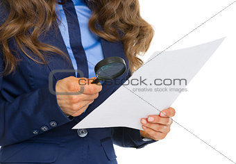 Closeup on business woman examining document using magnifying gl