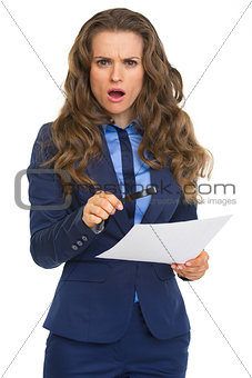 Surprised business woman with magnifying glass and document