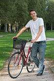 Young man standing next to his bike