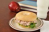 Tunafish sandwich on a bagel with schoolbooks