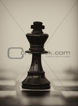Black wooden chess king on chess board