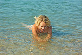 Teenage girl lies in shallow seawater