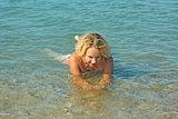 Teenage girl lies in shallow seawater