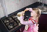 little girl putting pasta in the pot