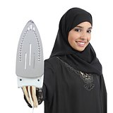Arab housewife woman smiling and holding a smoothing iron